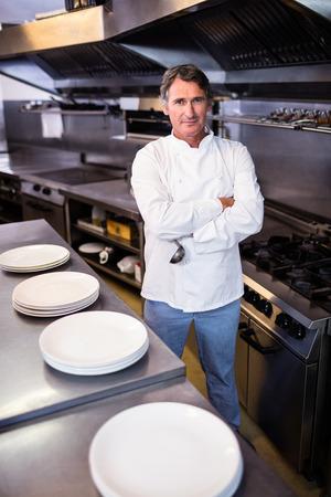mani incrociate: Ritratto del cuoco unico sorridente con le mani incrociate in cucina