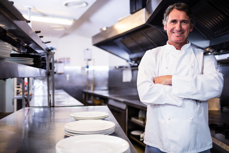 Portrait of smiling chef with hands crossed in the kitchen