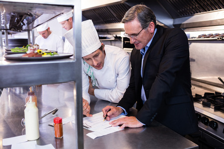 directeur du restaurant Homme écrit le presse-papiers tout en interagissant au chef de cuisine dans la cuisine commerciale