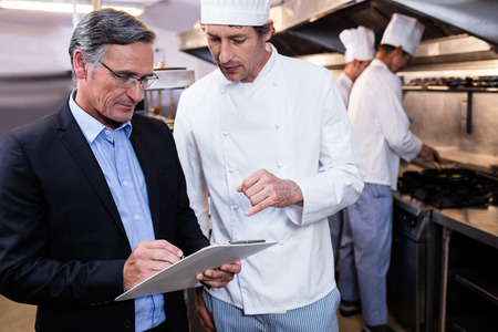 Male restaurant manager writing on clipboard while interacting to head chef in commercial kitchen Banque d'images