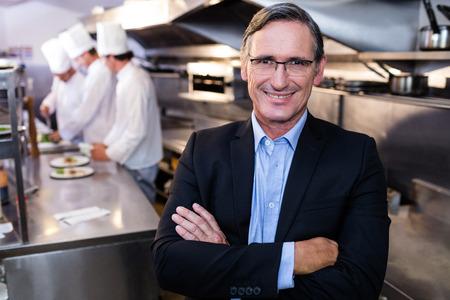 Férfi éttermi menedzser állt a fegyverekkel a kereskedelmi konyhában