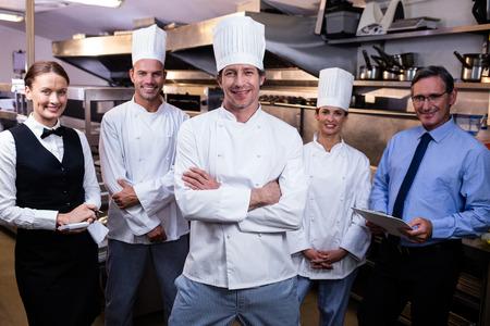 Portrait of happy restaurant team standing together in commercial kitchen Foto de archivo