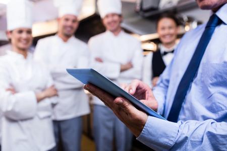 Střední část manažera restaurace používající digitální tablety v komerční kuchyni