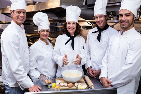 standing together: Portrait of happy chefs team standing together in commercial kitchen Stock Photo