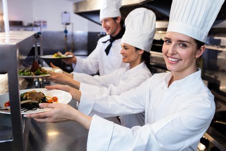 Chefs handing dinner plates through order station in the kitchen