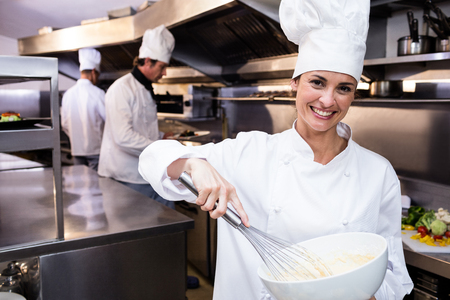 whisking: Portrait of happy chef whisking bowl of eggs in a commercial kitchen