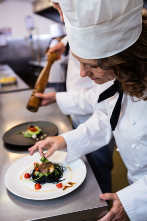garnishing: Female chef garnishing meal on counter in commercial kitchen