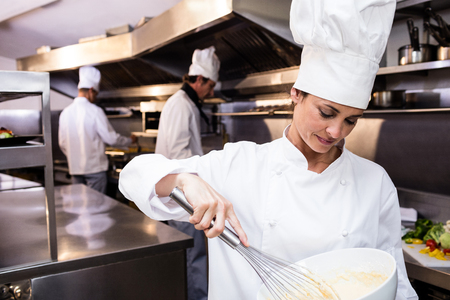 whisking: Chef whisking bowl of eggs in a commercial kitchen