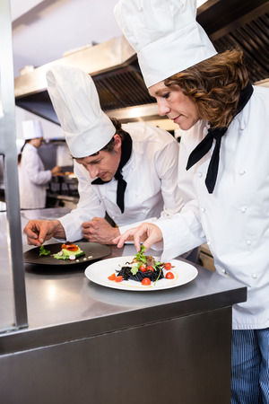 garnishing: Two chefs garnishing meal on counter in commercial kitchen Stock Photo
