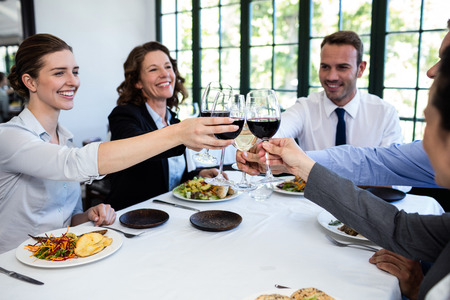 toasting wine: Group of businesspeople toasting wine glass during business lunch meeting in a restaurant