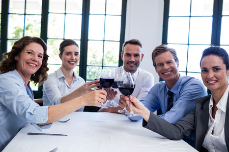 toasting wine: Portrait of businesspeople toasting wine glass during business lunch meeting in a restaurant Stock Photo