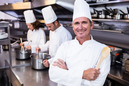 thee: Portrait of smiling chef in commercial kitchen and thee chefs cooking In background
