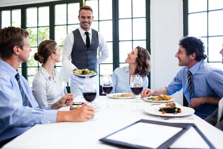 uniform attire: Waiter serving salad to the business people in restaurant