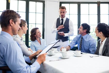 tomando refresco: Camarero hablar con la gente de negocios, teniendo un orden en el restaurante