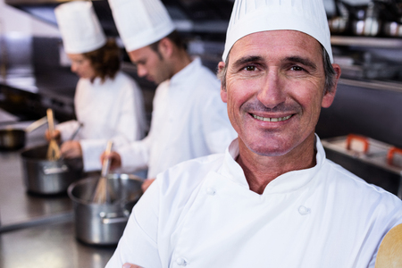 thee: Portrait of smiling chef in commercial kitchen and thee chefs cooking in background Stock Photo