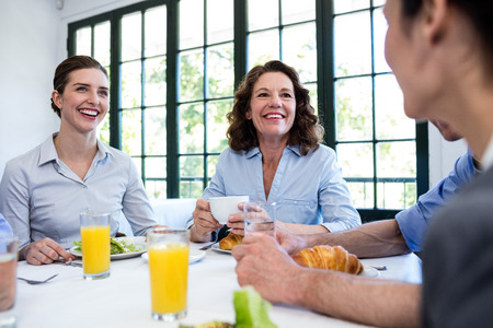formals: Business people in laughing while having lunch in restaurant