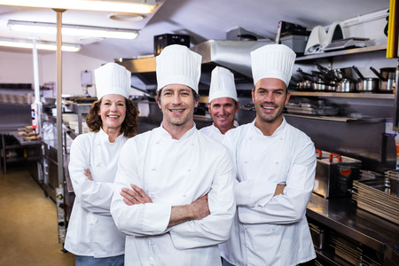 uniform clothing: Group of happy chefs smiling at the camera in a kitchen wearing uniforms Stock Photo