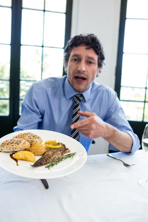 formals: Portrait of frustrated man sitting at table and holding a plate of meal in restaurant Stock Photo
