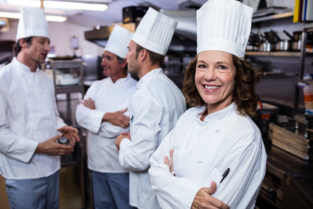 thee: Portrait of smiling chef in commercial kitchen and thee chefs discussing In background