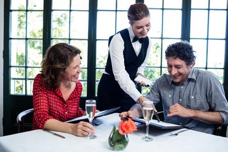 tomando refresco: Camarera ayudar a una pareja mientras que la selecci�n del men� de la tarjeta del men�