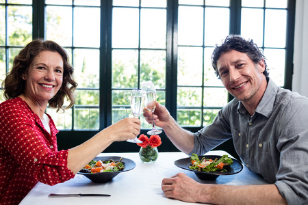 champagne flutes: Middle-aged couple toasting champagne flutes while having lunch in a restaurant