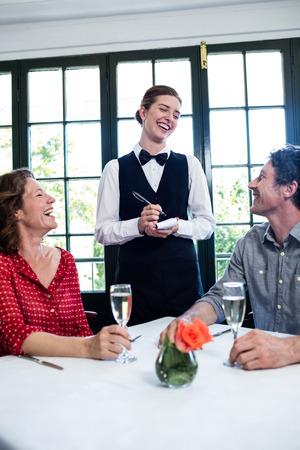 tomando refresco: camarera joven que r�e mientras que teniendo una orden de una pareja en el restaurante
