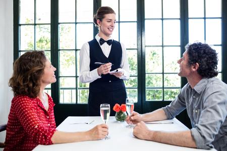 tomando refresco: camarera joven que toma una orden de un par en el restaurante
