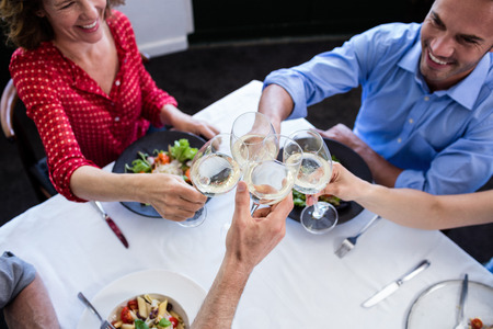 toasting wine: Happy friends toasting wine glass while having lunch in restaurant Stock Photo