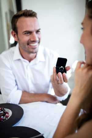 proposal: Man proposing to woman offering engagement ring in a restaurant