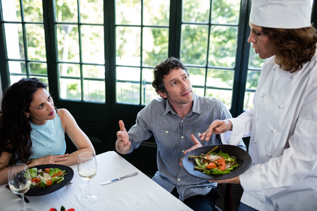 Couple complaining about the food to chef in a restaurant