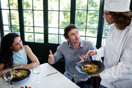 Pareja quejándose de la comida de chef en un restaurante
