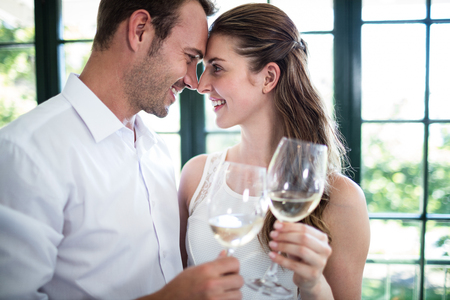toasting wine: Couple looking face to face and toasting wine glasses in a restaurant