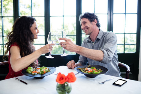 toasting wine: Couple toasting wine glasses at dining table in the restaurant Stock Photo