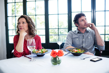 couple dating: Woman feeling bored and ignoring each other in restaurant Stock Photo