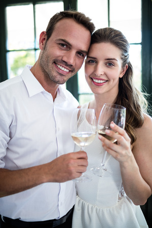 toasting wine: Portrait of couple toasting wine glasses in a restaurant
