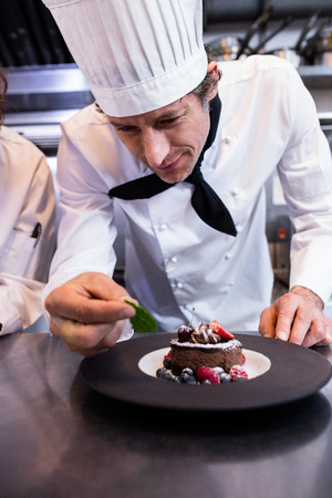 garnishing: Male chef garnishing dessert with a mint leaf in commercial kitchen Stock Photo