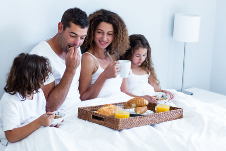 mid adults: Family having breakfast in bed at home Stock Photo