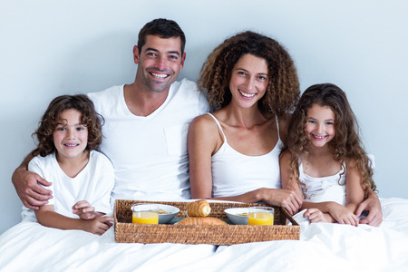 mid adults: Portrait of a family sitting with breakfast tray in bed at home