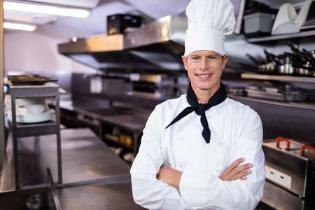 mani incrociate: Ritratto del cuoco unico fiducioso in piedi in cucina con le mani incrociate