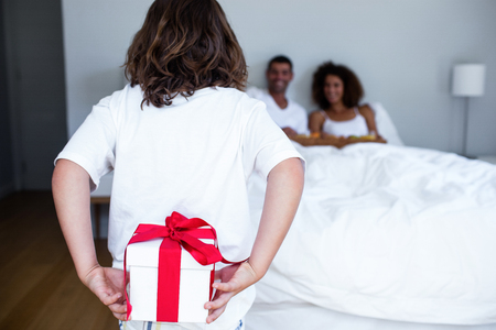 gift behind back: Son hiding gift behind his back for parents in bedroom Stock Photo