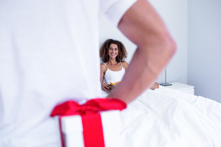 gift behind back: Man hiding gift behind his back for wife in bedroom Stock Photo