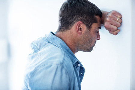 hand on forehead: Close-up of upset man leaning on wall with hand on forehead