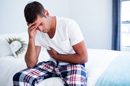 Fiatal férfi ül a gyomorfájás ágyon a hálószobában Stock fotó