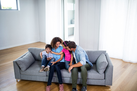 mum and daughter: Happy family sitting together on sofa in living room