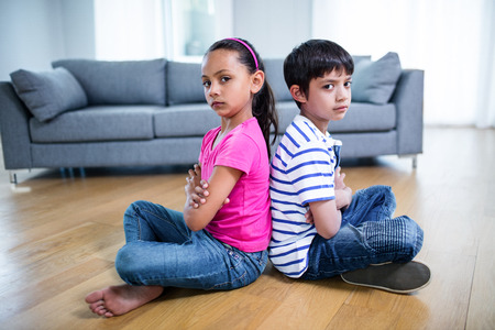 siblings: Portrait of upset siblings ignoring each other at home Stock Photo