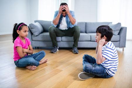 Zirytowany ojciec siedzący na kanapie, podczas gdy dzieci kłócą się i dokuczają sobie w domu