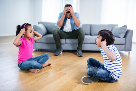 sibling rivalry: Annoyed father sitting on sofa while kids fighting and teasing each other at home