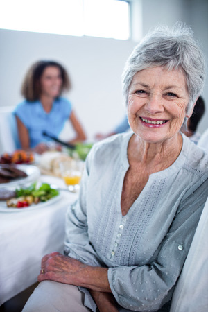 dinning table: Portrait of senior woman sitting at dinning table and family in background