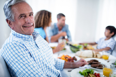 dinning: Portrait of senior man sitting at dinning table and family in background Stock Photo
