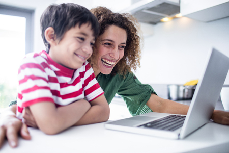 mixed race woman: Mother and son using laptop in kitchen at home Stock Photo
